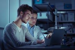 Studenti di ingegneria nel laboratorio alla notte Immagini Stock Libere da Diritti