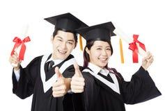 Studenti di istruzione dell'uomo e della donna di graduazione con il pollice su Immagini Stock Libere da Diritti
