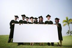 Studenti di laurea del gruppo all'aperto che tengono concetto del cartello Fotografia Stock Libera da Diritti