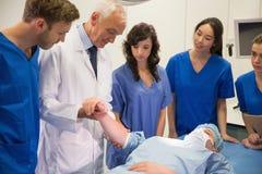 Studenti di medicina e professore che controllano impulso dello studente Immagini Stock