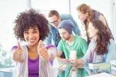 Studenti di modo con i pollici su Immagine Stock