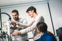 Studenti di robotica che preparano robot per le prove nel worksh Immagini Stock