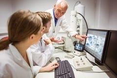 Studenti di scienza che esaminano immagine microscopica sul computer con il conferenziere Fotografia Stock