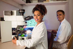 Studenti di scienza che lavorano in laboratorio uno che guarda tramite il microscopio Fotografie Stock