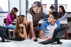 Studenti di Using Computer With dell'insegnante in aula Immagini Stock