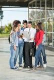 Studenti ed insegnante With Book Standing sull'istituto universitario Fotografia Stock Libera da Diritti