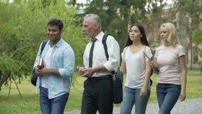 Studenti ed insegnante che camminano nel parco vicino all'istituto universitario, discutente progetto di scienza archivi video