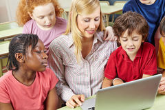 Studenti ed insegnante che lavorano con il computer portatile Immagine Stock