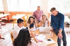 Studenti ed insegnante della High School con il computer portatile Immagini Stock Libere da Diritti