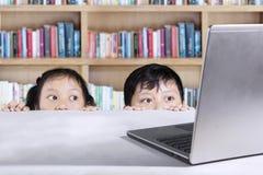 Studenti elementari che sbirciano computer portatile in biblioteca Immagine Stock Libera da Diritti