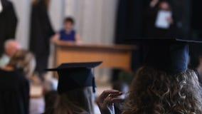 Studenti felici in cappelli ed abiti che guardano graduation, ricevente diploma video d archivio