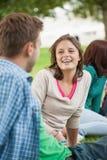 Studenti felici casuali che si siedono sulla chiacchierata dell'erba Fotografia Stock