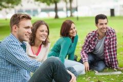 Studenti felici casuali che si siedono sulla risata dell'erba Fotografia Stock