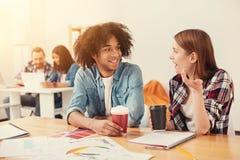 Studenti felici che comunicano mentre bevendo caffè Fotografia Stock Libera da Diritti
