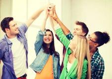 Studenti felici che danno livello cinque alla scuola Fotografia Stock Libera da Diritti