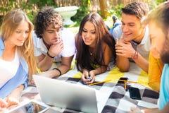 Studenti felici che esaminano computer portatile all'aperto Fotografie Stock Libere da Diritti