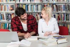 Studenti felici che lavorano con il computer portatile in biblioteca Fotografie Stock Libere da Diritti