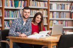 Studenti felici che lavorano con il computer portatile in biblioteca Fotografie Stock