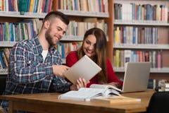 Studenti felici che lavorano con il computer portatile in biblioteca Immagini Stock