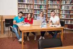 Studenti felici che lavorano con il computer portatile in biblioteca Immagini Stock Libere da Diritti