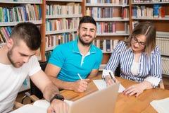 Studenti felici che lavorano con il computer portatile in biblioteca Fotografia Stock Libera da Diritti