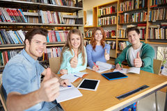 Studenti felici che mostrano i pollici su nella biblioteca di scuola Fotografia Stock