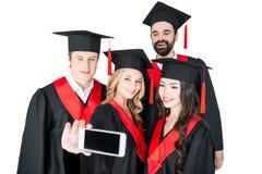 Studenti felici che prendono selfie sullo smartphone isolato su bianco Immagini Stock Libere da Diritti