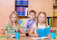 Studenti felici che si siedono ai loro scrittori nell'aula Fotografie Stock Libere da Diritti