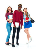 Studenti felici che stanno e che sorridono con i libri, il computer portatile e le borse Immagine Stock Libera da Diritti