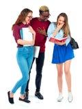 Studenti felici che stanno e che sorridono con i libri, il computer portatile e le borse Fotografie Stock