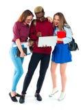 Studenti felici che stanno e che sorridono con i libri, il computer portatile e le borse Immagine Stock