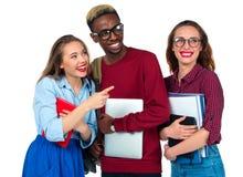 Studenti felici che stanno e che sorridono con i libri, il computer portatile e le borse Immagini Stock Libere da Diritti