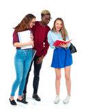 Studenti felici che stanno e che sorridono con i libri, il computer portatile e le borse Fotografia Stock Libera da Diritti