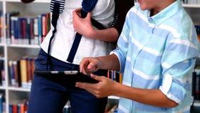 Studenti felici che utilizzano compressa digitale nella biblioteca video d archivio
