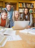 Studenti felici che utilizzano computer portatile allo scrittorio nella biblioteca Fotografia Stock Libera da Diritti