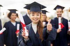 Studenti felici con i diplomi che mostrano i pollici su Fotografie Stock