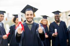 Studenti felici con i diplomi che mostrano i pollici su Immagine Stock Libera da Diritti