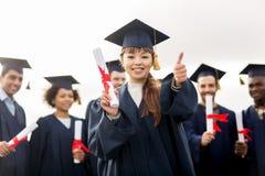 Studenti felici con i diplomi che mostrano i pollici su Fotografia Stock