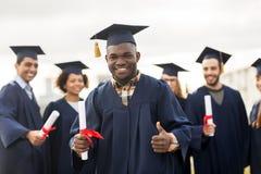 Studenti felici con i diplomi che mostrano i pollici su Fotografie Stock Libere da Diritti