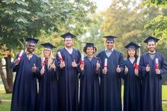 Studenti felici con i diplomi che mostrano i pollici su Immagini Stock Libere da Diritti