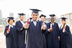 Studenti felici con i diplomi che mostrano i pollici su Fotografia Stock Libera da Diritti