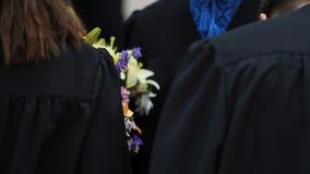 Studenti felici con i mazzi di fiori che ricevono le congratulazioni sulla graduazione stock footage