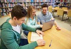 Studenti felici con il computer portatile ed i libri alla biblioteca Fotografia Stock