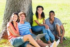 Studenti felici con il computer portatile sulla città universitaria Immagini Stock