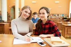 Studenti graziosi nella sala di lettura Fotografia Stock