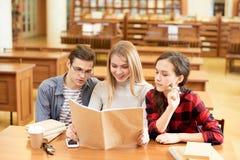 Studenti inquisitori che leggono il libro di scienza popolare Fotografie Stock