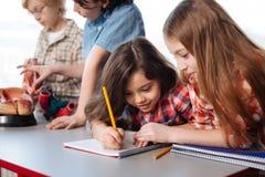 Studenti intelligenti attenti che scrivono una pubblicazione Fotografia Stock