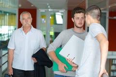 Studenti maschii adulti che parlano all'università Fotografia Stock Libera da Diritti