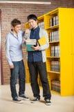 Studenti maschii che esaminano libro nella biblioteca di istituto universitario Fotografie Stock Libere da Diritti