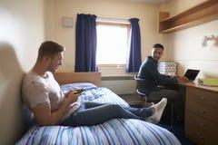 Studenti maschii che lavorano nella camera da letto della sistemazione della città universitaria Immagini Stock Libere da Diritti